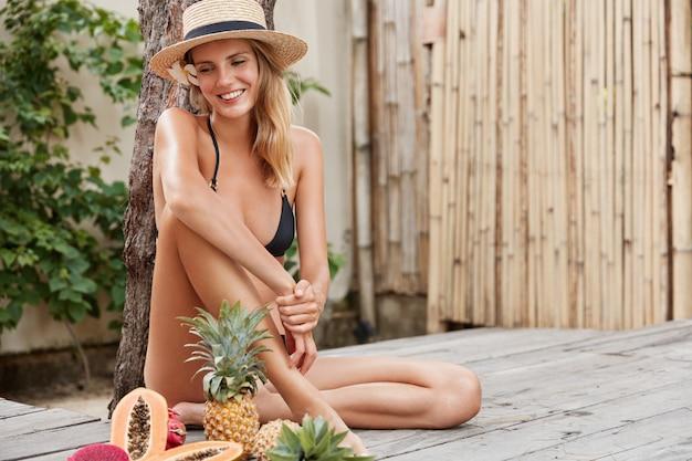 Glücklicher nachdenklicher weiblicher tourist, der in heißem tropischem land rekonstruiert, in der nähe von exotischen früchten sitzt, diät hält, ananas, papaya und drachenfrucht schmeckt. gesunder veganer lebensstil, entspannung und sommerruhe