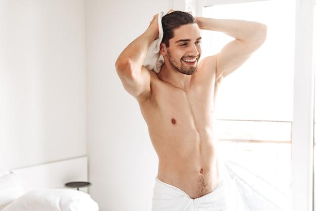 Glücklicher nackter mann, der drinnen im badezimmer steht