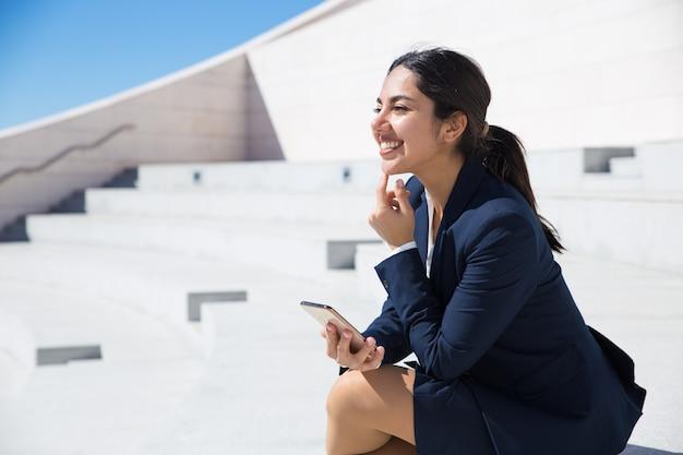 Glücklicher netter fachmann mit smartphone lustige szene genießend