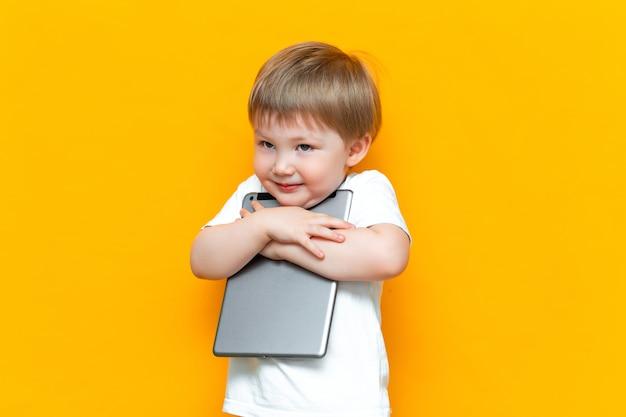 Glücklicher netter junge, der seinen reizenden tablet-computer-pc, z-generation, kinder umarmt, die mit technologie geboren wurden