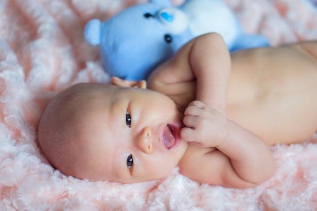 Glücklicher netter kleiner asiat 2 monate alte neugeborene babykind lächelt