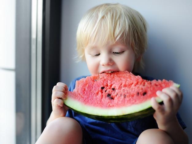Glücklicher netter kleiner junge, der die wassermelone sitzt auf fensterbrett isst. frisches bio-essen für kleinkinder