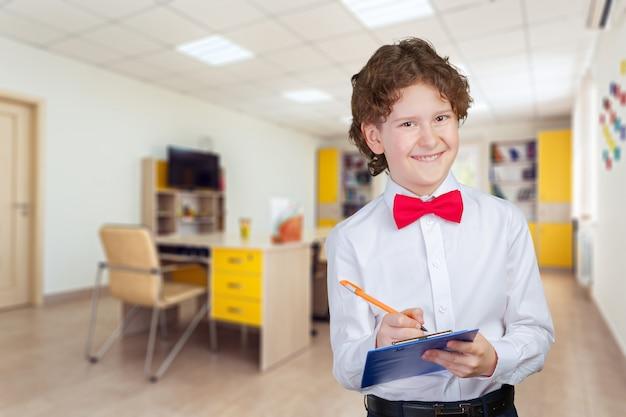 Glücklicher netter kluger junge in der schule. zum ersten mal in die schule. zurück zur schule.