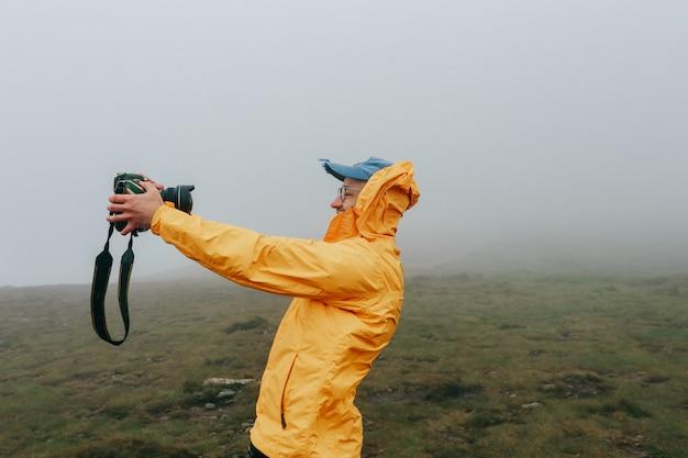 Glücklicher netter mann, der selfie am windigen tag mit nebel nimmt