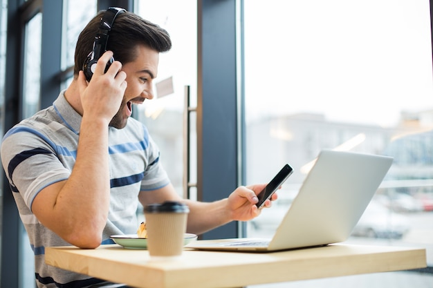 Glücklicher netter positiver mann, der sein smartphone hält und gefühle ausdrückt, während musik in den kopfhörern hört