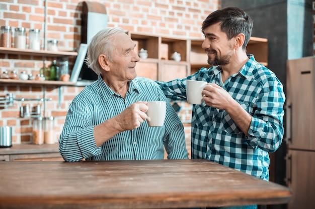Glücklicher netter positiver vater und sohn, die zusammen am tisch sitzen und lächeln, während sie tee zusammen trinken