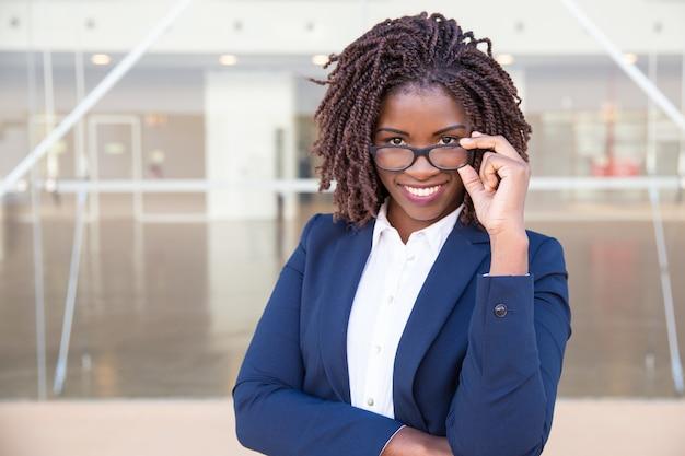 Glücklicher netter weiblicher büroangestellter, der draußen eyewear berührt
