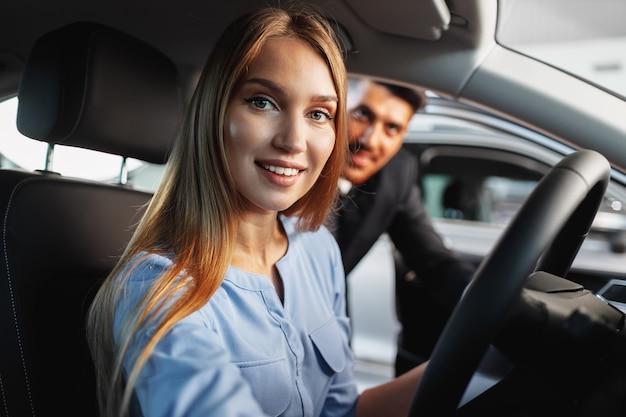Glücklicher neuwagenbesitzer der frau, der im fahrersitz sitzt und sich umschaut