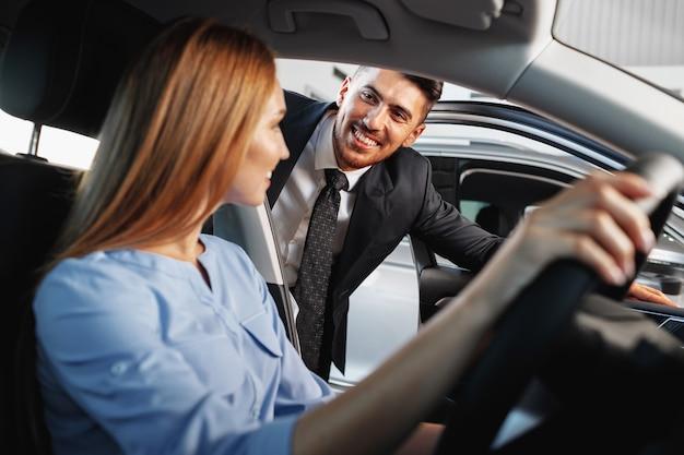 Glücklicher neuwagenbesitzer der frau, der im fahrersitz sitzt