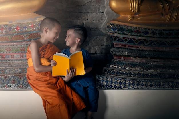 Glücklicher novizenmönch unterrichtet glückliche kleine kinder im tempel mit spaß am inhalt des dharma. atutthaya thailand