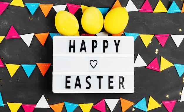 Glücklicher ostern-schriftzug auf weißer tafel mit filzgirlande und gelb gemalten eiern auf dunklem hintergrund