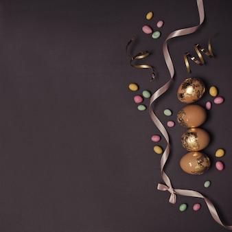 Glücklicher osternhintergrund mit goldenen dekor-eiern und mehrfarbigen roten gummibärchen des roten seidenbandes, glänzendes dekor auf einem dunklen tisch.