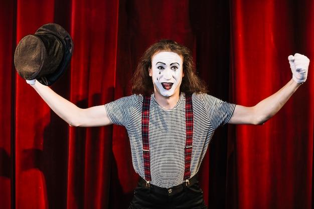 Glücklicher pantomime, der vor dem roten vorhang hält den hut biegt seinen muskel steht