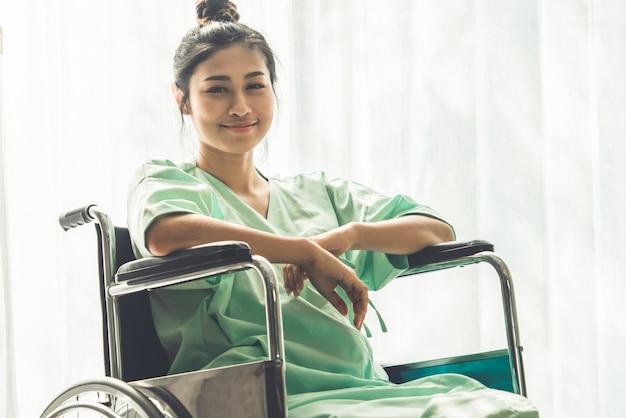Glücklicher patient, der auf rollstuhl im krankenhaus sitzt. medizinische gesundheitskonzept.