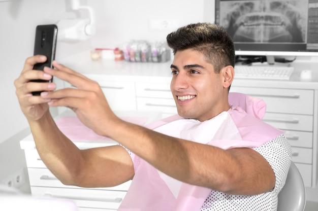Glücklicher patient, der ein selfie in der zahnklinik macht, hält smartphone und zeigt sein gesundes ...