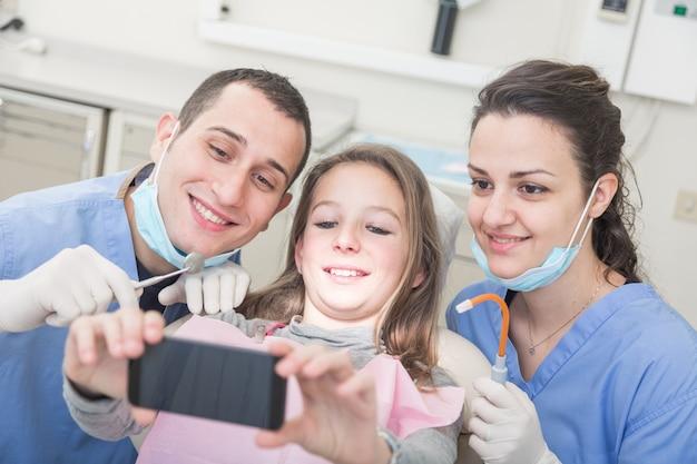 Glücklicher patient, zahnarzt und assistent, die alle zusammen selfie nehmen
