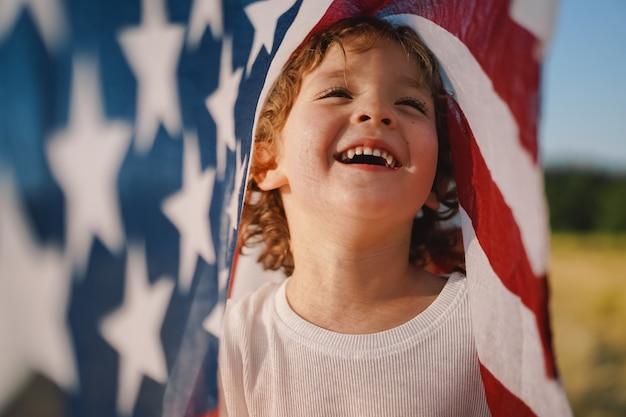 Glücklicher patriot des kleinen jungen, der auf dem gebiet mit amerikanischer flagge läuft. usa feiern den 4. juli