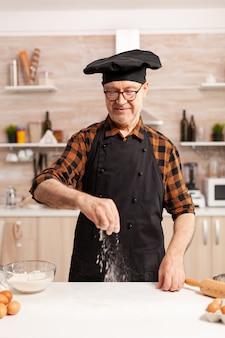 Glücklicher pensionierter koch, der hausgemachte pizza mit bio-weizenmehl zubereitet. seniorchef im ruhestand mit bone und schürze, in küchenuniform, die zutaten von hand durchsiebt.