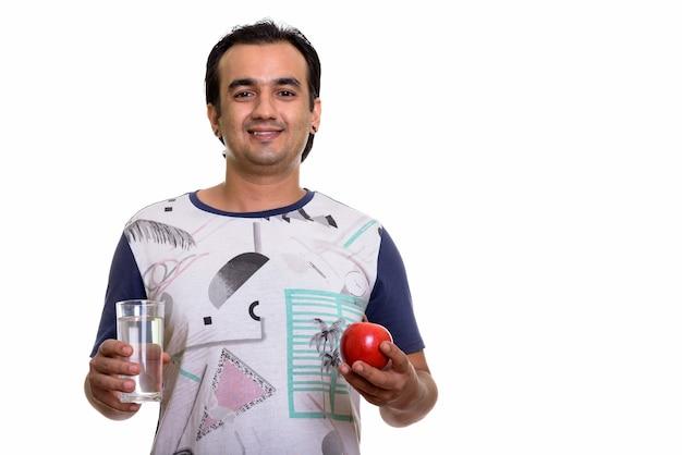 Glücklicher persischer mann, der roten apfel und glas wasser hält