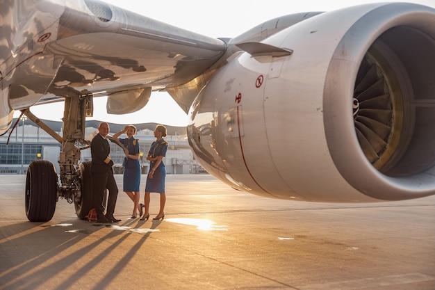 Glücklicher pilot und zwei hübsche stewardessen stehen zusammen, lehnen sich an ein flugzeug und lächeln nach der landung oder vor dem abflug in die kamera. flugzeuge, flugpersonal, besatzungskonzept