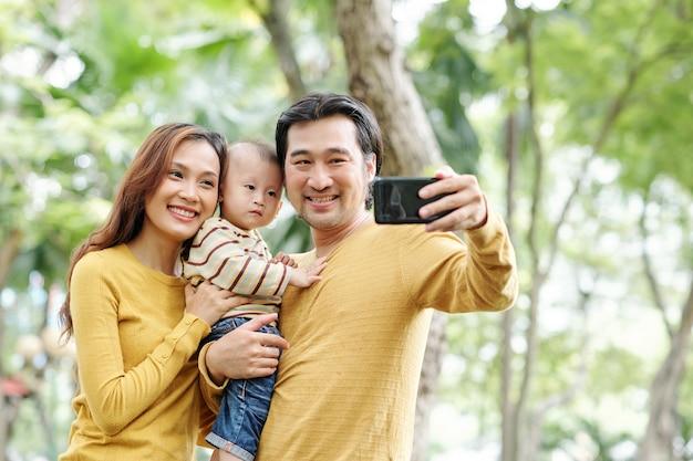 Glücklicher positiver asiatischer mann, der selfie mit seiner hübschen frau und entzückendem kleinen sohn nimmt
