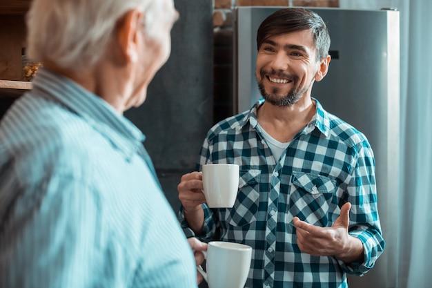 Glücklicher positiver entzückter mann, der eine tasse tee hält und zu seinem vater lächelt, während er die familiäre atmosphäre genießt