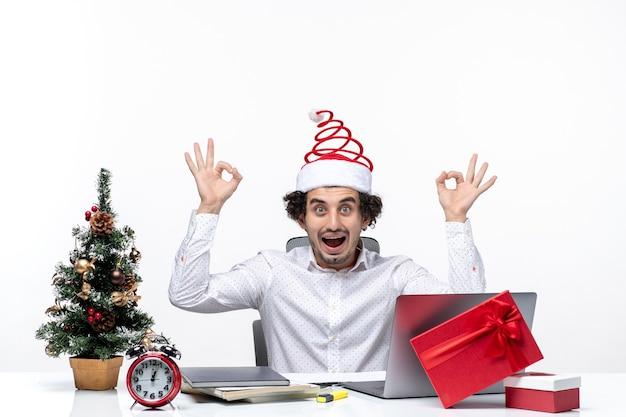 Glücklicher positiver junger geschäftsmann mit lustigem weihnachtsmann-hut, der brillengeste im büro auf weißem hintergrund macht