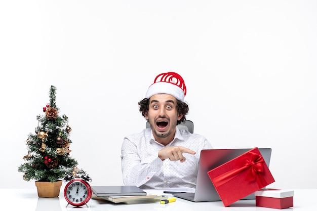 Glücklicher positiver junger geschäftsmann mit lustigem weihnachtsmannhut, der etwas auf laptop im büro auf weißem hintergrund zeigt