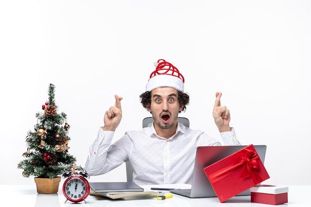 Glücklicher positiver junger geschäftsmann mit lustigem weihnachtsmannhut, der finger für glück im büro auf weißem hintergrund kreuzt