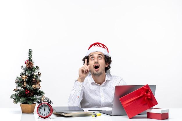 Glücklicher positiver junger geschäftsmann mit lustigem weihnachtsmannhut, der oben im büro auf weißem hintergrund schaut