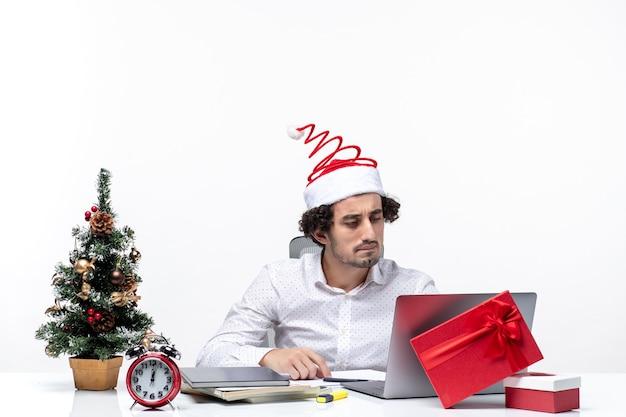 Glücklicher positiver junger geschäftsmann mit lustigem weihnachtsmannhut, der sein sorgfältig im büro auf weißem hintergrund prüft