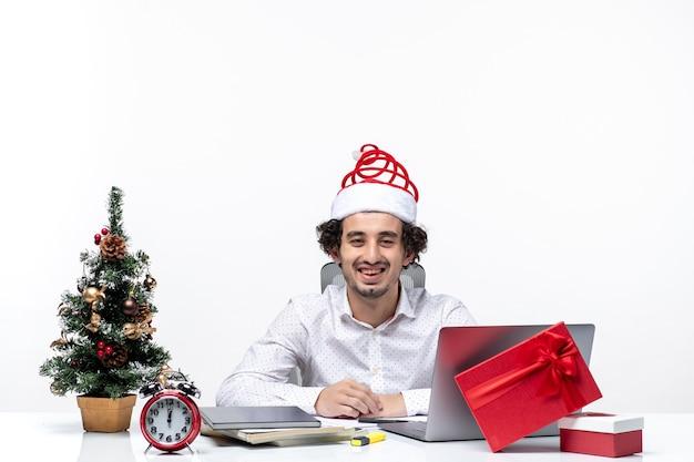 Glücklicher positiver junger geschäftsmann mit lustigem weihnachtsmannhut, der weihnachten im büro auf weißem hintergrund feiert
