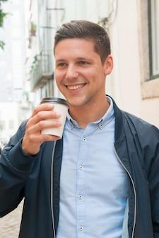 Glücklicher positiver student, der mitnehmerkaffee trinkt