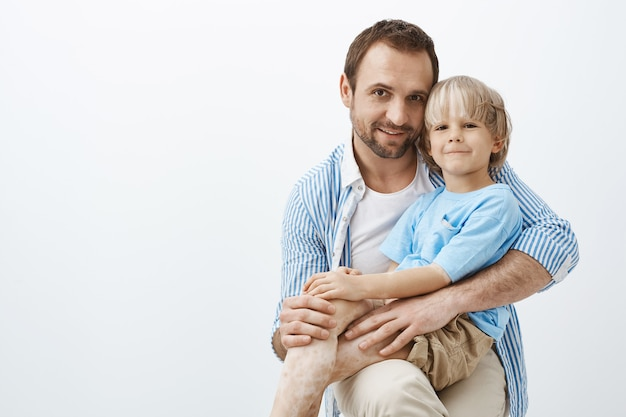 Glücklicher positiver vater und sohn mit vitiligo, die sich breit umarmen und lächeln, zufrieden und zufrieden sind, zeit miteinander zu verbringen