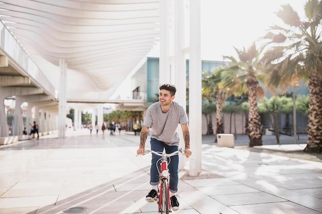Glücklicher radfahrer, der fahrt auf sein fahrrad genießt