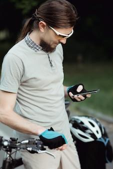 Glücklicher radfahrer in einer gelben sonnenbrille mit handy im park