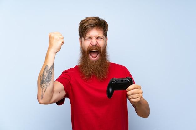 Glücklicher redheadmann mit dem langen bart, der mit einem videospielcontroller spielt