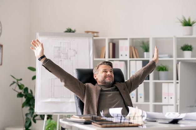 Glücklicher reifer architekt mit erhobenen armen, der vom schreibtisch im büro sitzt und pause mitten im arbeitstag genießt
