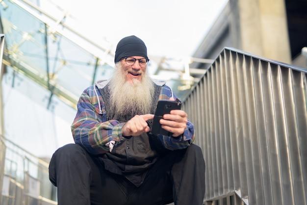 Glücklicher reifer bärtiger hipster-mann, der telefon am steg benutzt