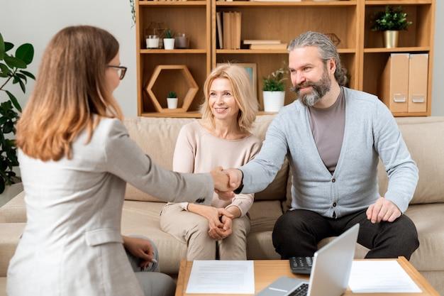 Glücklicher reifer bärtiger mann, der dem jungen immobilienberater hand gibt, nachdem er alle notwendigen papiere ausgehandelt und unterschrieben hat