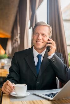 Glücklicher reifer geschäftsmann, der auf mobiltelefon mit tasse kaffee und laptop auf schreibtisch spricht