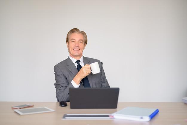 Glücklicher reifer geschäftsmann, der beim kaffeetrinken bei der arbeit denkt