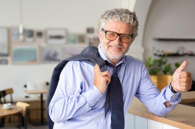 Glücklicher reifer geschäftsmann, der im bürocafé steht, sich auf theke stützt, jacke über schulter hält, daumen oben oder ähnlich zeigt