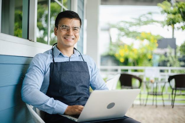 Glücklicher reifer geschäftsmann, der mit laptop in der cafeteria sitzt