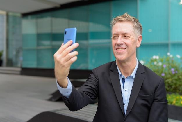 Glücklicher reifer geschäftsmann, der selfie nimmt und in den straßen der stadt sitzt