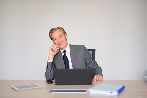 Glücklicher reifer geschäftsmann im anzug, der am telefon bei der arbeit spricht