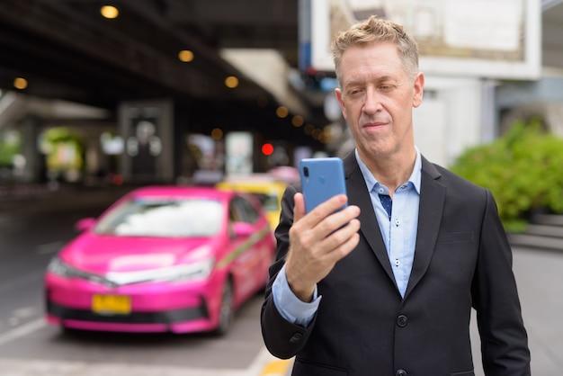 Glücklicher reifer geschäftsmann im anzug mit telefon an der taxistation