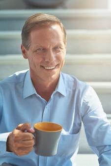 Glücklicher reifer geschäftsmann im hemd, das eine tasse kaffee hält, die kamera anschaut und lächelt, während er