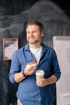 Glücklicher reifer geschäftsmann in der freizeitkleidung, die getränk und cupcake hält, während er im büro steht und kaffeepause genießt