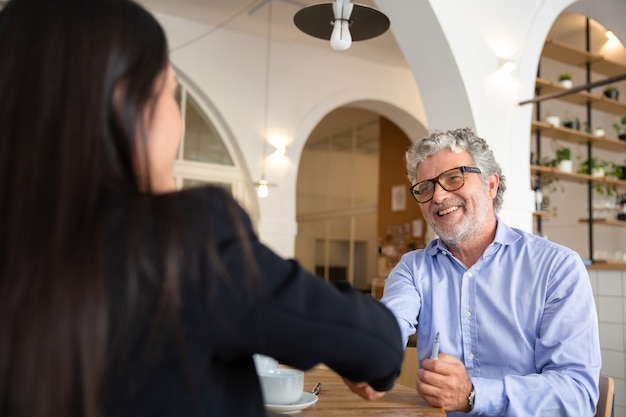 Glücklicher reifer geschäftsmann in gläsern, die hand mit weiblichem partner beim treffen im gemeinsamen arbeitsraum schütteln